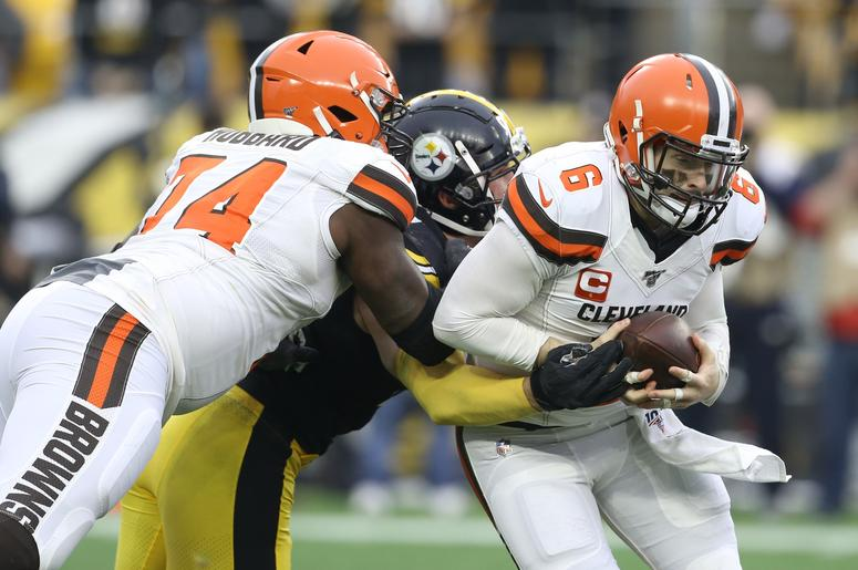 Cleveland Browns quarterback Baker Mayfield (6) scrambles away from Pittsburgh Steelers outside linebacker T.J. Watt (90) as offensive tackle Chris Hubbard (74) blocks during the second quarter at Heinz Field.