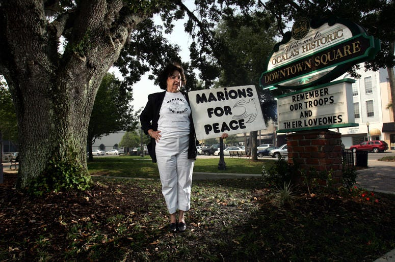 "Delphine Herbert, 71, stands in the town square in Ocala, Florida, where she holds protest on the weekend. The sign, ""MARIONS FOR PEACE,"" references Marion County residents. (Photo by Charles Trainor Jr./Miami Herald/MCT/Sipa USA)"