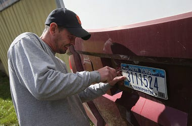 Man removing New York license plate
