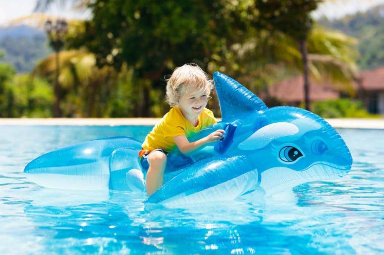 Kid on shark pool toy