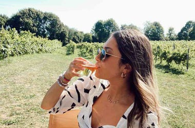 Sabrina drinking wine in vineyard