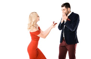 Attractive woman proposing surprised boyfriend with ring