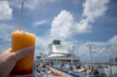 Orange and Mango Cocktail on on a cruise liner being held by a Caucasian mans left hand on beautiful tropical beach.