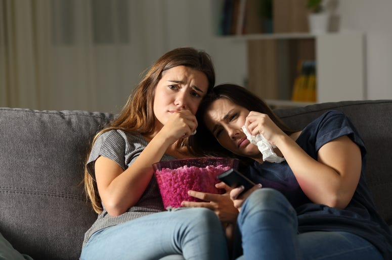 Two sad friends crying watching tv in the night