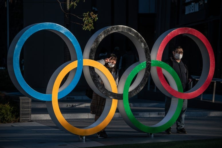 People wearing face masks pose for photographs next to Olympic Rings in Tokyo, Japan. The 2020 Olympic Games are postponed.