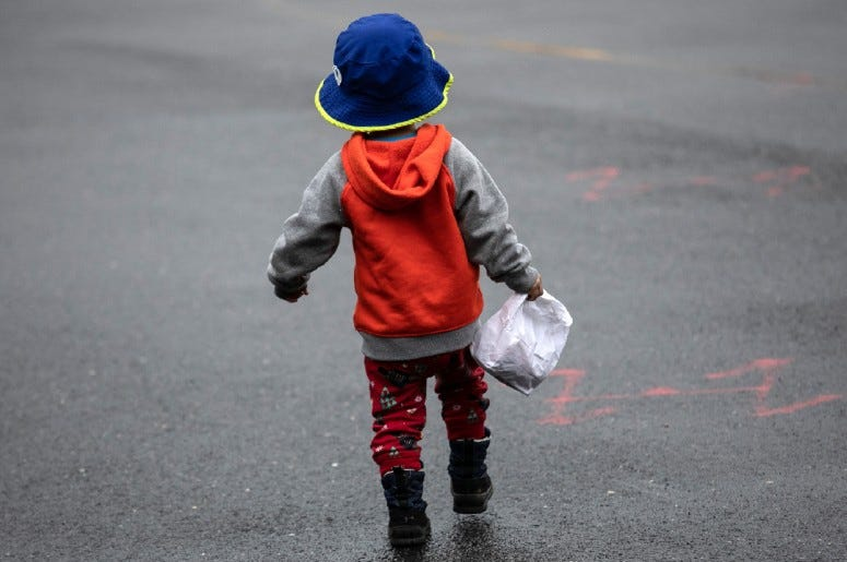 A young boy carries a meal bag. Schools across the country are providing food for kids out of school during the coronavirus pandemic.