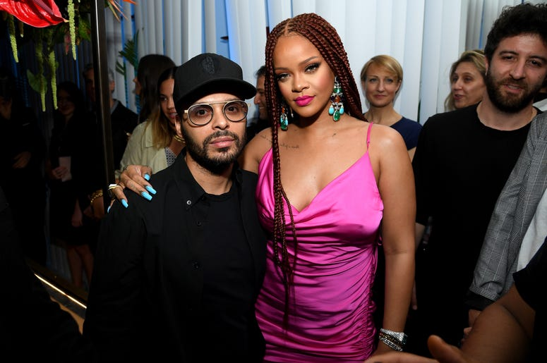 Rihanna poses in a magenta strappy dress and long burgundy braids at the New York pop-up shop event for her Fenty clothing line.