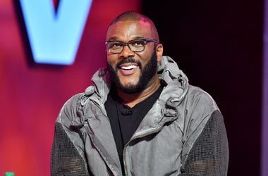 Tyler Perry poses smiling on stage at Essence Festival 2019.
