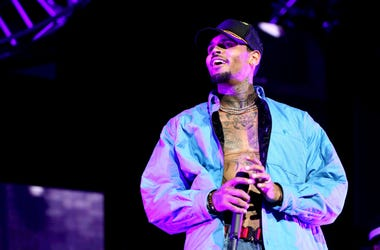 Chris Brown holds mircrophone and smiles while performing at 2018 BET Experience.
