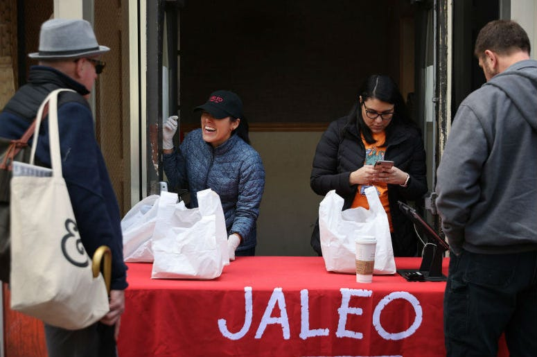 People purchase carry-out lunches out of the back door of celebrated Chef José Andres' Jaleo restaurant in response to the novel coronavirus March 17, 2020 in Washington, DC.