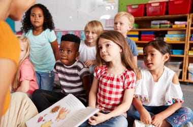 Young children gather together in front of a teacher, who is reading a book.