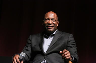 """John Singleton sits in a chair smiling at a discussion at the """"Spotlight On Screenwriting: Boyz n the Hood 25th Anniversary Screening With John Singleton And Walter Mosley"""" presented by The Academy Of Motion Picture Arts And Sciences."""