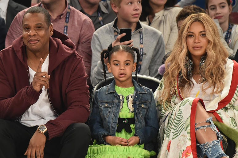 Jay Z, Blue Ivy Carter and Beyoncé sit courtside at a basketball game.