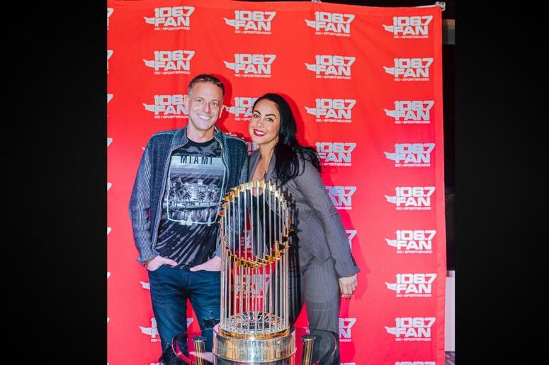 Jason Kidd and Corinna Delgado from 94.7 The Drive pose with the trophy.