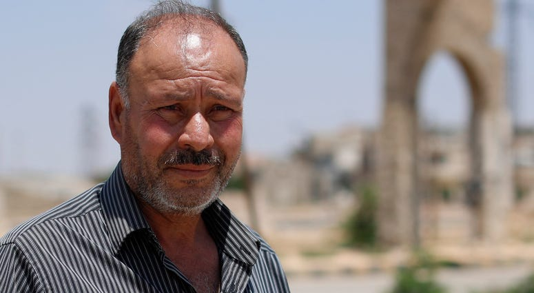 In this Tuesday, July 17, 2018, photo, Col. Omar Melhem, 51, who defected from the Syrian army defector and once commanded a rebel faction of some 3,000 fighters speaks during an interview with The Associated Press in the central Syrian town of Talbiseh,
