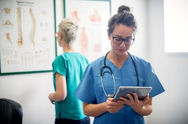 Two professional nurses in office looking through some medical procedure.