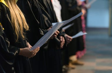 Choir singers holding musical score and singing on student graduation day in university, college diploma commencement - stock photo