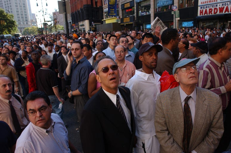 People watch World Trade Center burn September 11, 2001 after two hijacked airplanes slammed into the twin towers in New York City. (Photo by Spencer Platt/Getty Images)