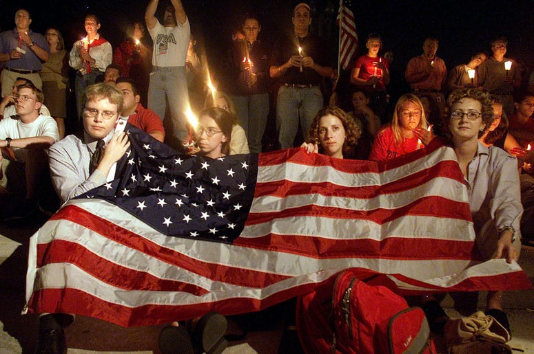 People cover themselves with an American Flag on the US Capitol grounds during a candle light vigil to remember victims who lost there life in the recent terorist attacks September 12, 2001 in Washington DC. (Photo by Mark Wilson/Getty Images)