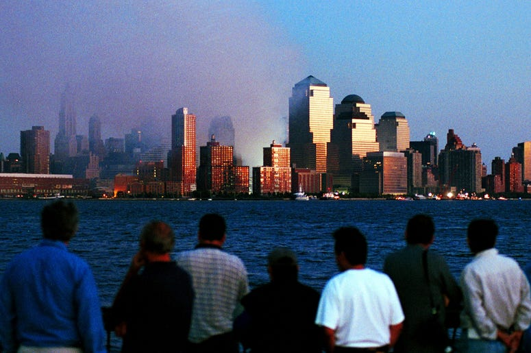 People watch smoke emit from the former site of the World Trade Center September 12, 2001 in Hoboken, N.J. Smoke filled the air all over lower Manhattan in the aftermath of Tuesday's terrorist attack and destruction of the World Trade Center. (Photo by Ch