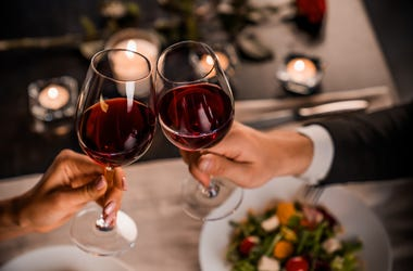 Close up of young couple toasting with glasses of red wine at restaurant - stock photo