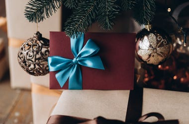 Gift voucher in burgundy envelope with blue bow under the christmas tree