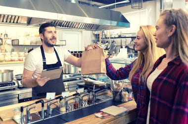 Waiter serving takeaway food to customers at counter in small family eatery restaurant - trendy fast food smiling owner delivering an online to go order in recycled paper bag to clients - stock photo