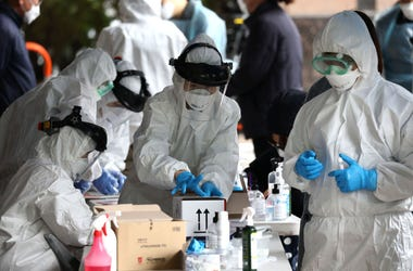 SEOUL, SOUTH KOREA - MARCH 10: Medical staff, wearing protective gear, take samples from people at a building where 46 people were confirmed to have the coronavirus (COVID-19), at a temporary test facility on March 10, 2020 in Seoul, South Korea. Accordin