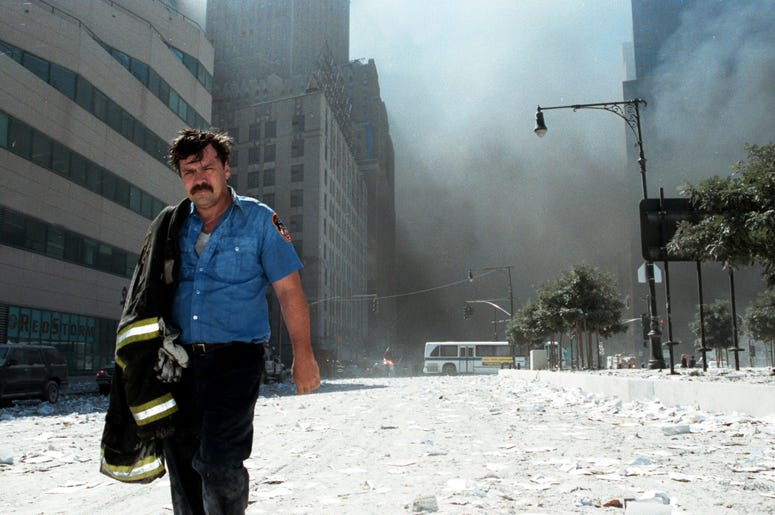NEW YORK - SEPTEMBER 11: An unidentified New York City firefighter walks away from Ground Zero after the collapse of the Twin Towers September 11, 2001 in New York City. The World Trade Center's Twin Towers and the Pentagon were attacked by terrorists usi