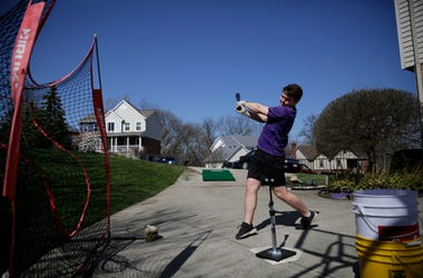 Kory Klingenbeck, a senior at Elder High School, practices hitting off a tee in his parents' driveway in Delhi Township, Ohio, on Wednesday, March 25, 2020. With schools closed, the Klingenbeck brother have attempted to continue workouts together at their