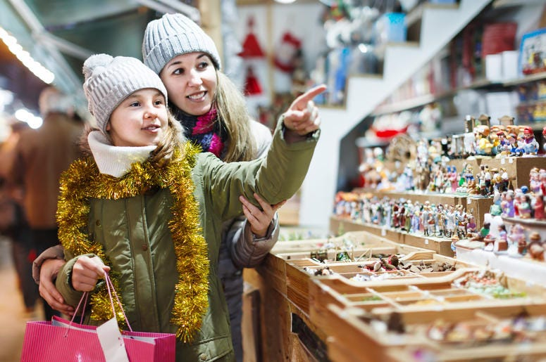 Girl with woman choosing Christmas gifts for family
