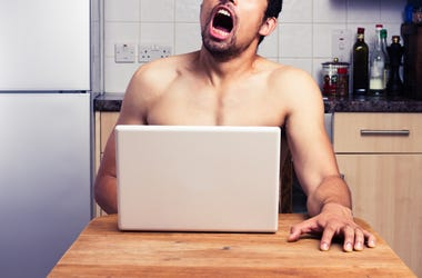 guy watching adult content in kitchen on computer