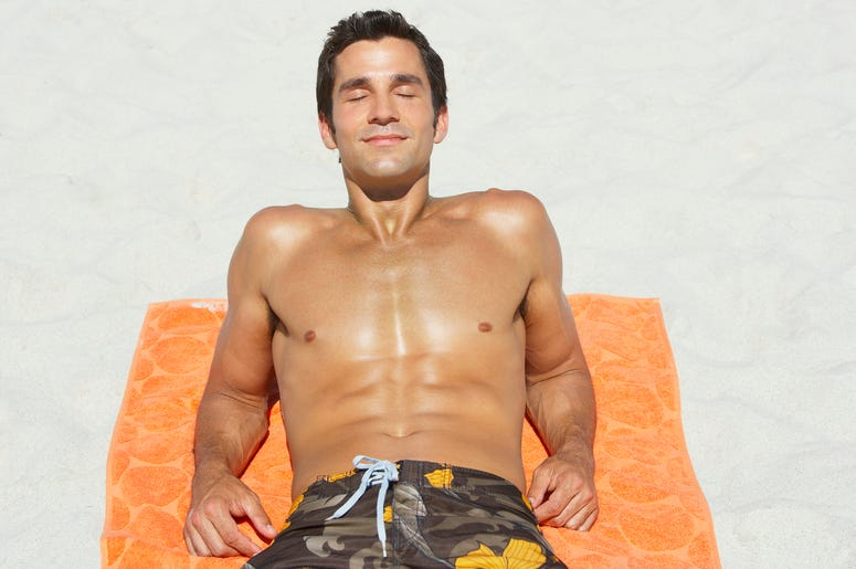 man tanning on beach
