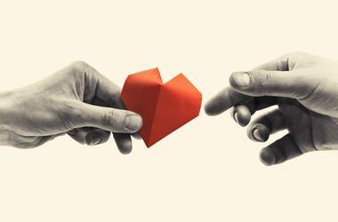 hands exchanging paper heart