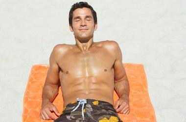 man tanning on beach