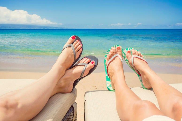 women lounging on beach in flip flops