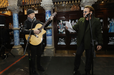U2's The Edge and Bono take part in the annual Christmas Eve busk on Grafton Street, Dublin