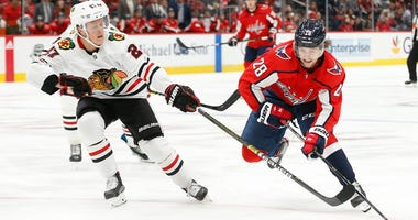 Blackhawks defenseman Adam Boqvist, left, defends against Capitals winger Brendan Leipsic (28).