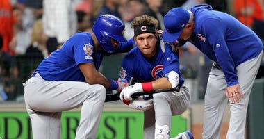 Cubs center fielder Albert Almora Jr. (5, center) is consoled by right fielder Jason Heyward (22, left) and manager Joe Maddon (70) after a fan was hit by a foul ball of his.