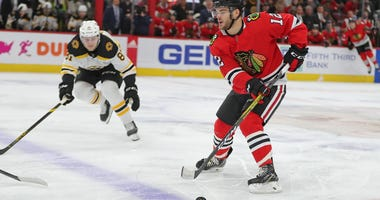 Blackhawks winger Alex DeBrincat (12) passes the puck as Bruins winger Anton Blidh (81) pursues him.