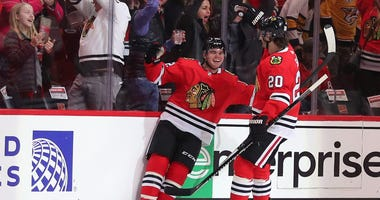 Blackhawks winger Alex DeBrincat (12) celebrates with winger Brandon Saad (20) after scoring a game-winning goal against the Predators.