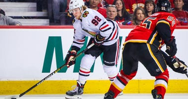 Blackhawks winger Alex Nylander (92) controls the puck against the Calgary Flames.