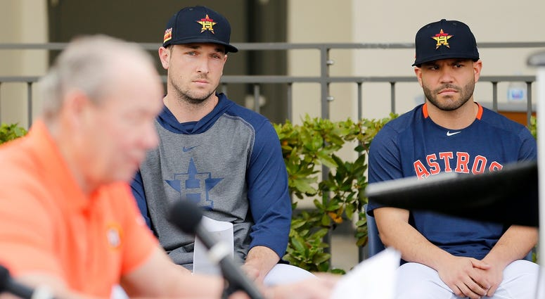 Astros third basman Alex Bregman, left, and second baseman Jose Altuve look on as owner Jim Crane, foreground, speaks at a press conference addressing the team's cheating scandal.