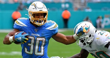 Chargers running back Austin Ekeler, left, runs with the ball against the Dolphins.