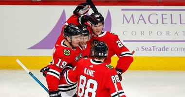 Blackhawks center Dominik Kahun (center) is congratulated by teammates after scoring against the Wild.