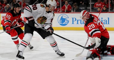Blackhawks forward Brandon Saad (20) attempts to shoot the puck by Devils goalie Mackenzie Blackwood (29).