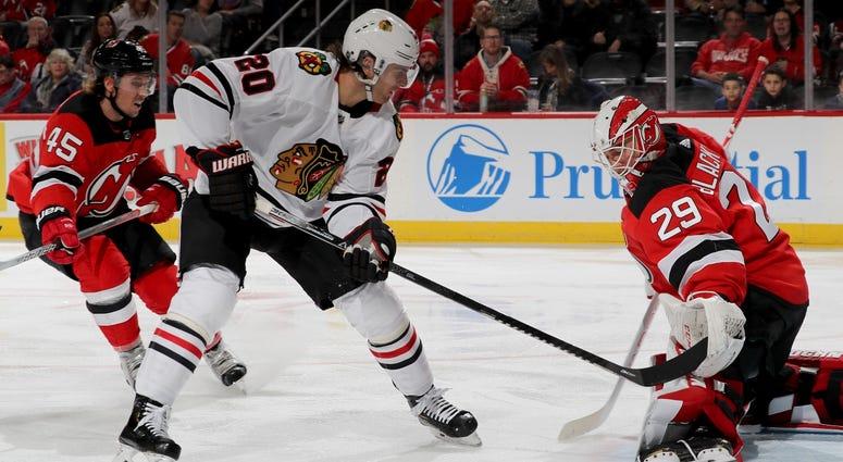 Blackhawks forward Brandon Saad (20) attempts to shoot the puck by Devils goalie Mackenzie Blackwood (29).