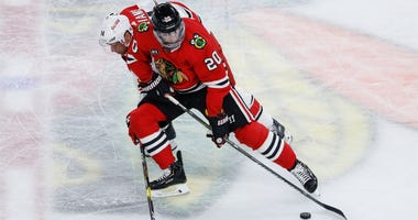 Blackhawks winger Brandon Saad (20) battles for the puck against Hurricanes winger Justin Williams (14).