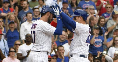 Anthony Rizzo (right) is greeted by Cubs teammate Kris Bryant after hitting a three-run home run against the Marlins.