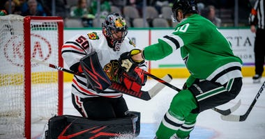 Blackhawks goalie Corey Crawford (50) makes a save in front of Stars winger Corey Perry (10).